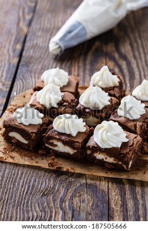 Cheesecake brownies with cream cheese swirled frosting and pastry tip in background - stock photo