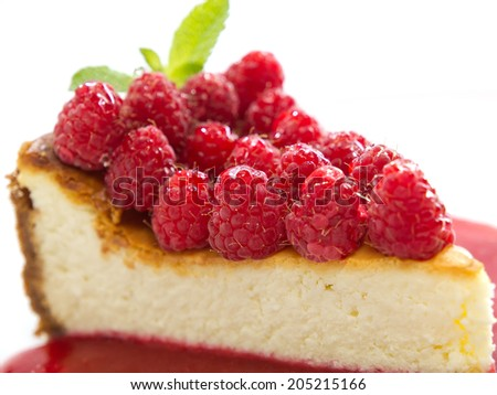 Cheesecake slice with fresh raspberries and mint isolated on white