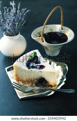 Cheesecake with currant and mint leaf on a wooden background