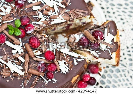 Cheesecake with missing slice baked with dried sweetened cranberries and covered in melted chocolate. Garnished with chocolate shavings, mint and sugar coated cranberries. Shallow DOF. - stock photo