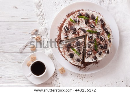 cheesecake with pieces of chocolate cookies and coffee close-up on the table. Horizontal view from above