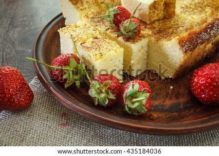 Cheesecake with strawberries. On a wooden table strawberries and linen napkin
