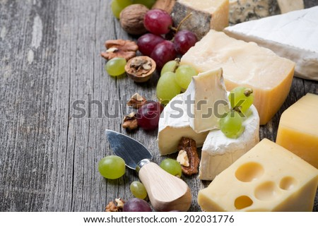 cheeses, grapes and walnuts on a wooden background, horizontal, close-up