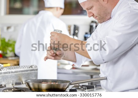 Chef adding pepper on steak in the kitchen - stock photo