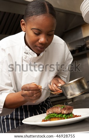 Chef Adding Sauce To Dish In Restaurant Kitchen - stock photo