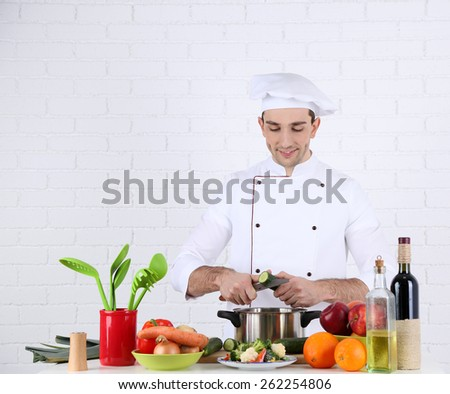 Chef at table with different products and utensil in kitchen on white wall background - stock photo