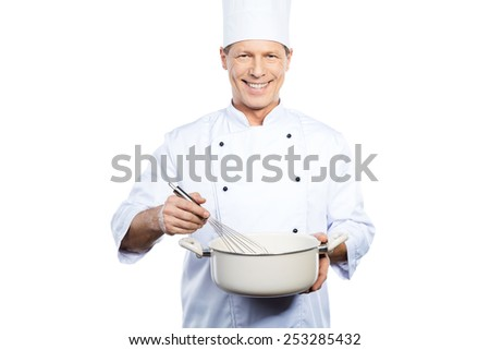 Chef at work. Cheerful mature chef in white uniform mixing something in casserole while standing against white background - stock photo