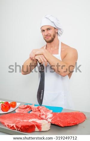 chef bodybuilder preparing large chunks of raw meat. - stock photo