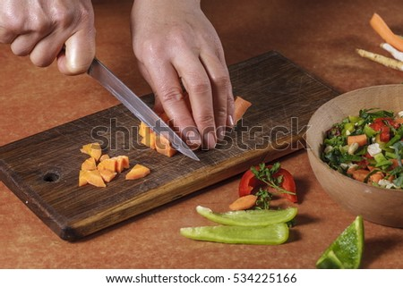 Chef chopping  vegetables on kitchen board