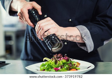 Chef cook in restaurant kitchen peppering salad, crop on hands, filtered image