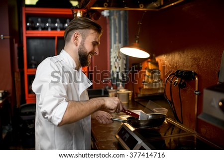 Chef cook in white uniform cooking with frying pan on the restaurant kitchen. Image with soft focus and small depth of field - stock photo