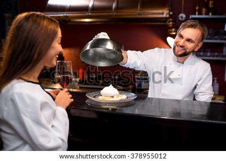 Chef cook in white uniform picking up cloche and showing dessert to female client on the bar table at the open kitchen of the restaurant. Soft focus image with small depth of field - stock photo