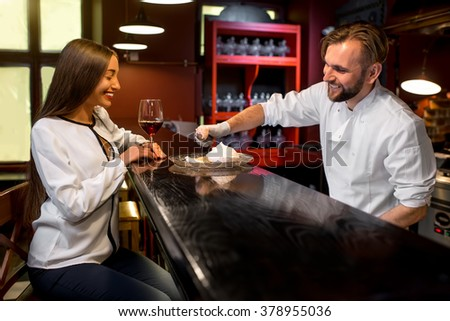 Chef cook in white uniform putting ice cream ball on the dessert to female client on the bar table at the open kitchen of the restaurant. Soft focus image with small depth of field