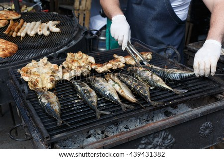 Chef cookind at grill grate. Plenty of chicken tabaka and mackerel fish grilled at barbecue. Mackerel and whole chicken bbq outdoors at picnic, party. Street food, meat and fish grill takeaway