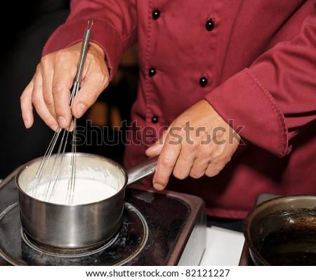 Chef cooking cream sauce on stove - stock photo