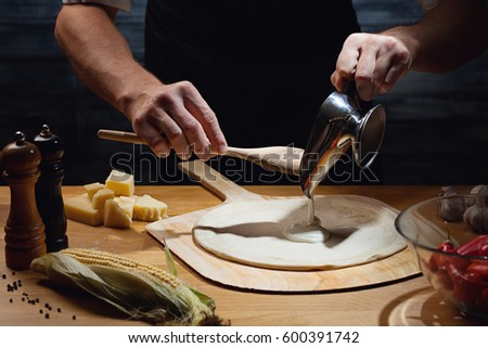 Chef cooking pizza, putting white sauce on pizza base. Low key shot, close up of hands, some ingredients around on table.