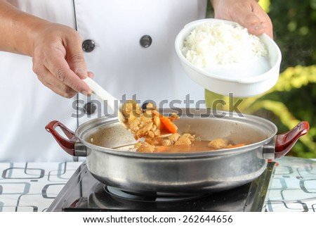 chef cooking pork curry and  vegetables  in outdoor kitchen