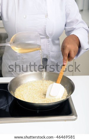 Chef cooking risotto pouring white wine into the pan - stock photo