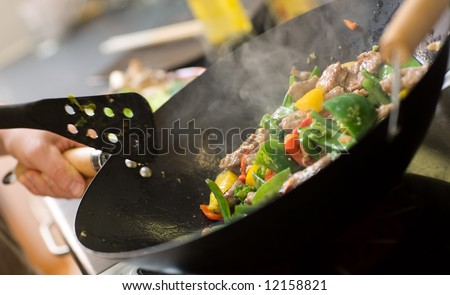 Chef cooking vegetables and meat in wok pan - stock photo