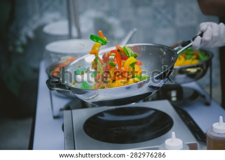 Chef cooking vegetables in wok pan. Shallow dof - stock photo