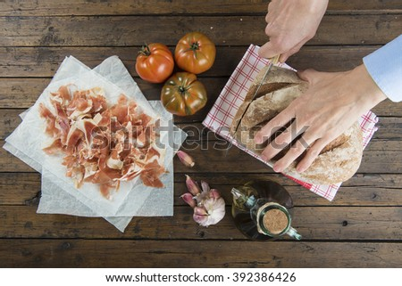 Chef cutting a slice of bread to prepare a toast with ham, olive oil, garlic and tomato - stock photo