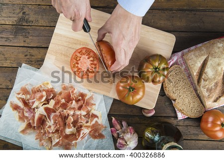 Chef cutting a tomato with a knife to prepare a toast of ham, garlic and olive oil - stock photo