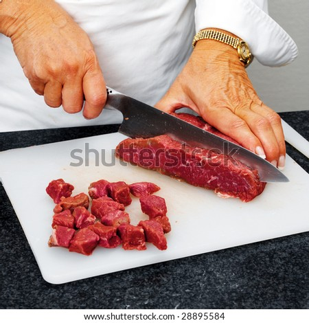 Chef cutting beef