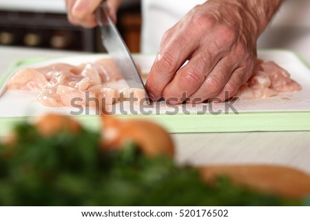 Chef cutting chicken fillet. Making Chicken and Egg Galette Series.