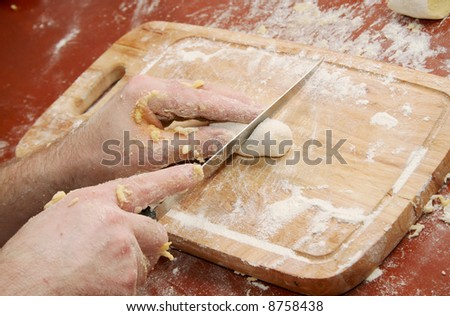 Chef cutting dumpling on the board