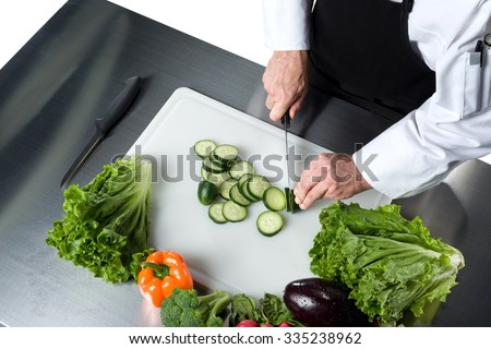 chef cutting fruits and vegetables on a chopping board - stock photo