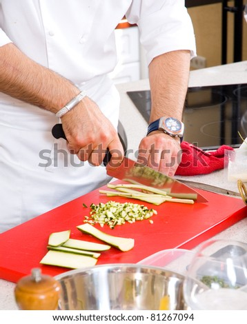 Chef cutting the zucchini on a board - stock photo