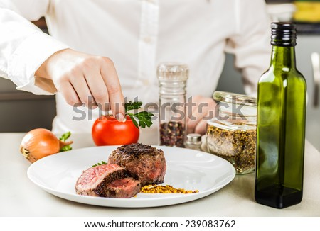 chef decorates greens ready fried medallions in a plate - stock photo