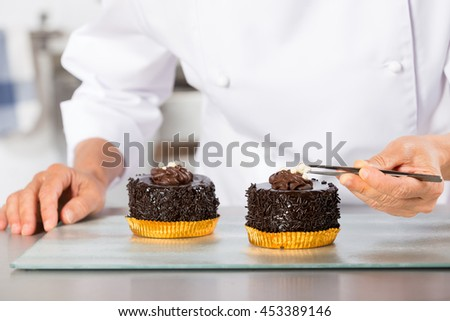 Chef decorating finishing two cakes of chocolate and cream