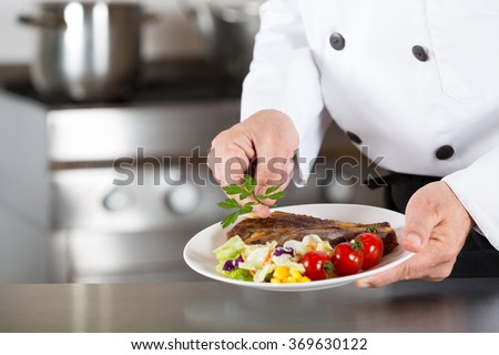Chef finishing her plate and almost ready to serve at the table