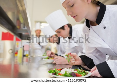 Chef finishing her salad in culinary class in kitchen - stock photo