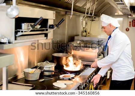 Chef frying a dish in hotel kitchen - stock photo