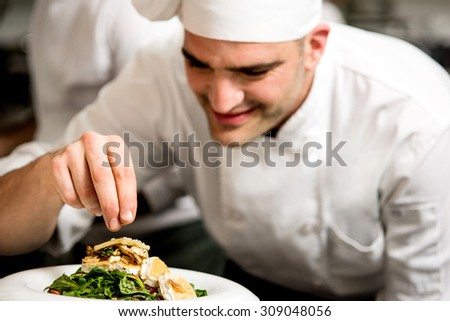 Chef garnishing a salad of roast goat cheese - stock photo