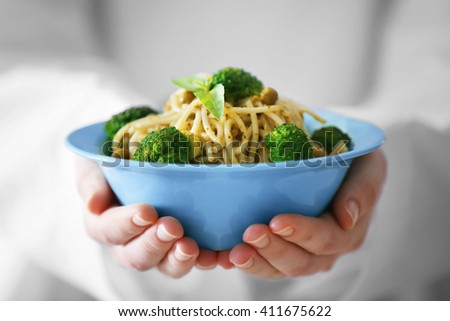 Chef hands holding delicious cold pasta salad in bowl closeup - stock photo