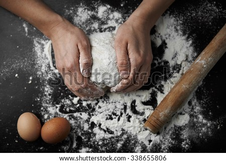 Chef hands kneading raw dough on the board in bakery. Woman cook preparing bread or pastry.  - stock photo