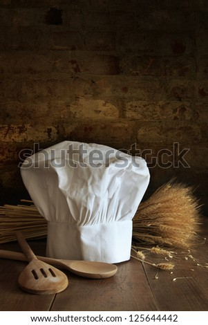 Chef hat and wooden spoons and wheat with brick background - stock photo