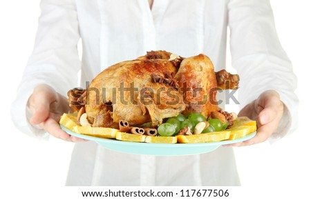 Chef holding a plate of baked chicken with fruit and spices close-up