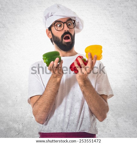 Chef holding colorful peppers - stock photo