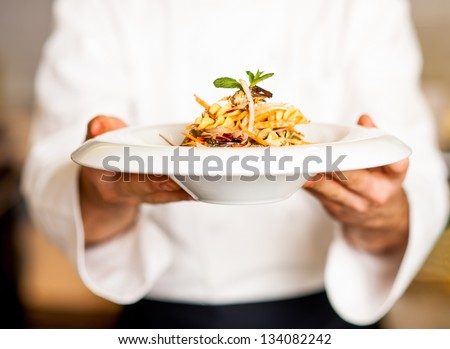 Chef holding mouth watering pasta salad, ready to serve. - stock photo