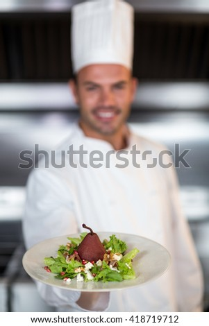 Chef holding plate with food while standing in commercial kitchen - stock photo