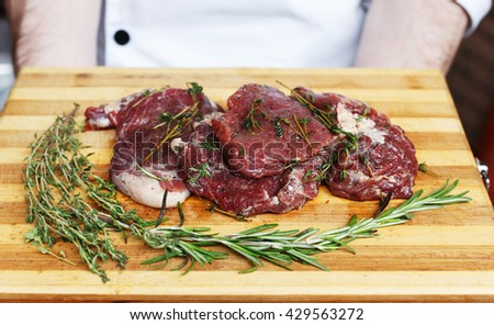 Chef holds fresh pork steak ready for BBQ cooking. Raw meat on a cutting board with rosemary leaf. Raw pork meat on wood, closeup. Marinated in spices raw steak for barbecue. - stock photo
