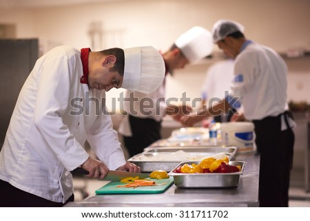 chef in hotel kitchen  slice  vegetables with knife and prepare food - stock photo