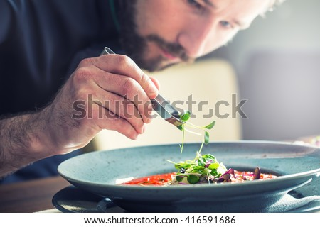 Chef in hotel or restaurant kitchen cooking, only hands. He is working on the micro herb decoration. Preparing tomato soup. - stock photo