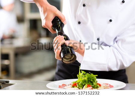 Chef in hotel or restaurant kitchen cooking, only hands to be seen, he is seasoning dishes