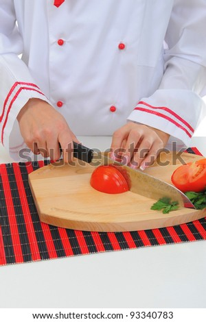 Chef in uniform cuts the tomato in the kitchen.