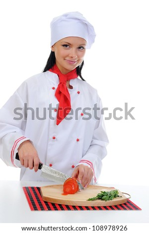 Chef in uniform cuts the tomato in the kitchen. Isolated on white background - stock photo
